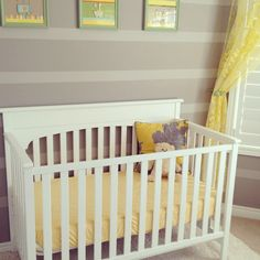 Two tone grey walls in nursery with yellow accents.