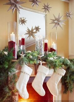 Think about what you can do above and below a mantel. Here, tall glass containers show off candles tucked in mounds of cranberries or small ornaments. Greens and bell-trimmed stockings finish the lower part of the arrangement, but it's the glittering multipoint stars hung on fishing line above that make this mantel sparkle.
