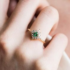 The Skylar Ring from Emi Conner features a stunning round emerald, surrounded by four glimmering marquise CZ stones, and eight round white CZ. Emerald approx Eight round CZ Four marquise cut CZ yellow gold band width Crystal Engagement Rings, Emerald Wedding Rings, Emerald Ring Vintage, Ruby Engagement Ring Vintage, Pretty Engagement Rings, Green Emerald Ring, Crystal Ring, Emerald Jewelry, Alternative Engagement Rings