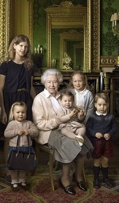 (front L) Cheeky little Mia Tindall can be seen proudly holding up her great-granny's Launer handbag in a moment, says one who was there, that was totally unscripted. 'The moment with Mia was completely spontaneous, it was not staged at all. She just picked up her great-granny's handbag and that was it,' they said. (L-R) Lady Louise Windsor, The Queen cuddling 11-month-old Princess Charlotte of Cambridge, Savannah Phillips and Prince George of Cambridge