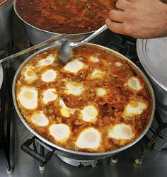 shakshouka - dish of eggs poached in a sauce of tomatoes, chili ...