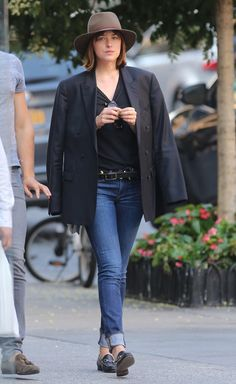 Dakota Johnson wears a black tee, a brown fedora, cuffed blue jeans and Gucci loafers