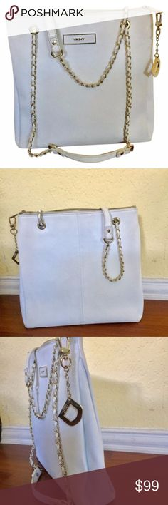"""DKNY  Saffiano Leather Convertible White Tote Bag DKNY Donna Karan Large White Saffiano Leather Convertible Tote/Shoulder/Cross-body Bag Retail: $365 Features: Saffiano Leather Solid White Gold-tone Hardware DKNY Insignia plate Large """"D"""" Removable Bag/Key Fob Full zipper top closure Duel chain with leather trim convertible handles Embossed satin interior lining 2 interior zipper pockets w/leather pulls 2 interior slip pockets  Condition: Normal wear for a pre-loved bag. Random scuffs here…"""
