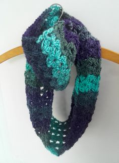 Ladies infinity scarf wool cowl.  Perfect accessory for the cooler months. I have crocheted this scarf in a 100% pure wool Aran using a lacey stitch to give it a nice drape. Due to the nature and colours of the yarn the scarf is completely unique.  The scarf is versatile and can be worn wrapped around the neck two times, as a long scarf or used as a hood.  The scarf measures approximately 6 inches in width and 44 inches circumference.  The yarn used is 100% wool, the scarf should be…