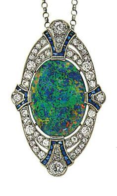 An early 20th century opal, diamond and sapphire brooch, by Dreicer, circa 1920. The central oval cabochon opal within an old brilliant-cut diamond pierced oval surround with old-cut diamond and calibré sapphire fan shaped quarters. Signed Dreicer & Co #Vintage #Dreicer