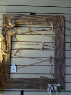 Old, rustic barn wood made into a picture frame with twine and clothespins. Accented with burlap flower and bow
