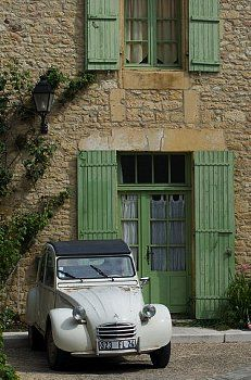An old Deux Chevaux car parked in front of an old village house, Dordogne…