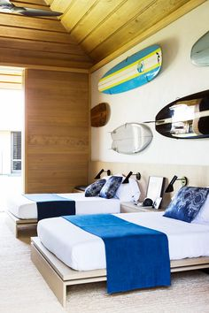 This beach-to-bedroom look photographed by Laure Joliet is pure surfer's paradise. A rad surfboard gallery wall makes a splash above the beds, playing off deep-blue ocean-inspired...