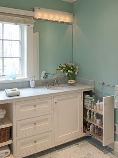 Elizabeth used a combination of open and closed storage to provide efficient organization in this master bath. Open shelves offer easy access to towels, while pullout drawers, a tall cabinet and a full-height pullout cabinet conveniently store toiletries, beauty items, cleaning products and everyday essentials.