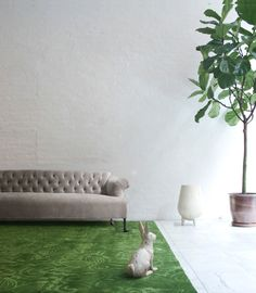 Hotel lobby couch with grass rug, rabbit sculpture and indoor plant.