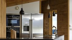 The chrome fridge-freezer sets the tone in this highland retreat - we also love the lighting! Croft 103 - Hill Cottage is a luxury self-catering holiday home in Durness, Scotland #chrome #kitchen #lighting #scotland #industrialdesign