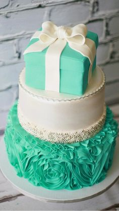 A 3-tier Wedding Cake, one with design, plain, and a present display on top.