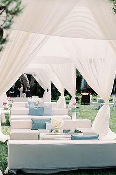 Sheer white drapes are curtained off to shield slender couches in a column-style seating arrangement, protecting guests from the sun and creating a dreamy look.