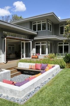 Outdoor living room recessed into the yard with a gravel floor and loose rock edging