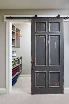 Distressed Barn Door. An old door, painted in Benjamin Moore HC-166 Kendall Charcoal is hung on barn door hardware as a sliding barn door to conceal the laundry room. Mike Schaap Builders