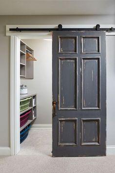 Distressed Barn Door. An old door, painted in Benjamin Moore HC-166 Kendall Charcoal is hung on barn door hardware as a sliding barn door to conceal the laundry room. Mike Schaap Builders