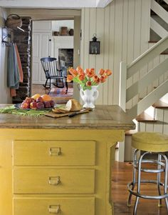 A SMALL VIEW OF A  C1780 HOME KITCHEN INTERIOR.  TULIPS IN A MILK GLASS URN-SHAPED VASE.