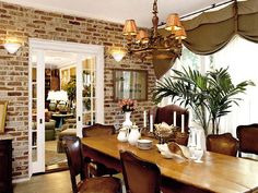 Combining different design elements can be a challenge. The space shown here works well for several reasons. The room's good bones--exposed brick, French doors, and glass walls--are allowed to shine. The furnishings and decorative accents highlight rather than dominate. Also, the warm mix of wood finishes softens the area. Don't be afraid to combine mahogany, oak, cherry, satinwood, and maple pieces if the blend feels harmonious. (Photo: Photo: Jean Allsopp; Stylist: Cari South)