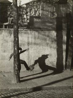 Child kicking ball by André Kertész (1930)