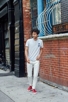 Isaac wears J. Crew jeans and Superga sneakers