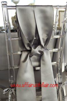 Silver satin chair ties were uniquely tied around this lucite chivari chair.