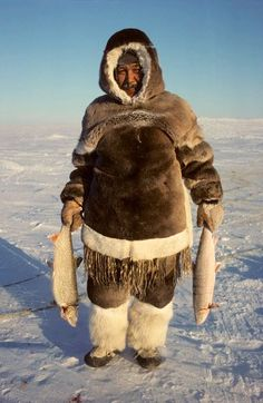Nutarariaq, an Inuit hunter, with his catch of Arctic Char and Lake Trout. Igloolik, Nunavut, Canada.: images from Bryan & Cherry Alexander Photography.