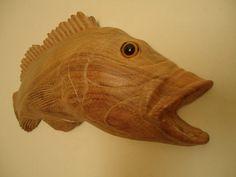 Peixe Tucunaré Entalhado em madeira de qualidade e resistente, com tratamento anti-cupins e encerada para dar brilho a madeira, NÃO é pintada. Pode ficar em ambiente internos ou externos. Muito bem detalhada e realista. Linda peça de decoração. Peça feita 100% a mão. Tamanhos: 55 cm de comprimento / 19 cm de altura / 4 cm de profundidade. Preço: 160,00 reais Quantidade: Feito Sob Encomenda Frete Não Incluso Trabalhamos com vários tipos de madeiras. Aceitamos encomendas em outros tamanhos.