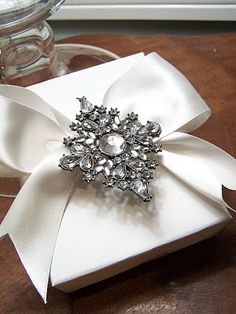 Add a beautiful satin bow and a brooch to embellish a gift. So elegant! #giftwrapping