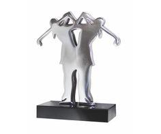 Peça: bidimensional, 16cm de altura.  Materiais disponíveis: alumínio (prata) ou bronze (dourado ou patinado).  Base: madeira natural ipê ou madeira revestida de fórmica preta, 12x6x2cm.  Placa cortesia: aço inox (prata) ou latão (dourada), 6x2cm.