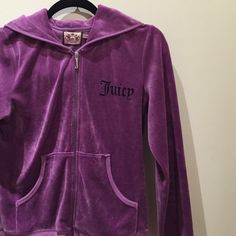 """Juicy Couture Velour Hoodie Preowned Original fit track jacket. Hooded collar. Long sleeves. Front pouch pocket. Full zipper closure with J-pull. Embellished back detail. Measures 22"""" from shoulder to hem 78% cotton, 22% polyester Worn a few times. In very good condition. I feel that the jacket runs a bit small so a Large would be perfect for a true medium Juicy Couture Sweaters"""