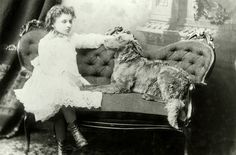 Helen Keller as a young girl, sitting on a couch, her large dog Jumbo sitting next to her. Age 8