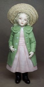 Adèle, wears a pale peach dress, trimmed with a white collar… over she wears a pale green coat, with double collar, four buttons and two patch pockets with buttons.