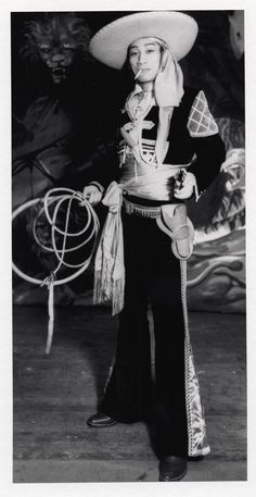 Kwan Duk Hing plays a cowboy holding lasso in one hand and gun in the other in 1930s. Museum of Performance and Design, Performing Arts Library/Calisphere.