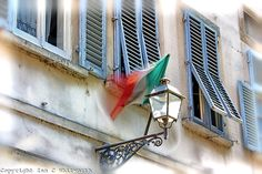 Looking up in an Italian street at the flag blowing in front of the window shutters.