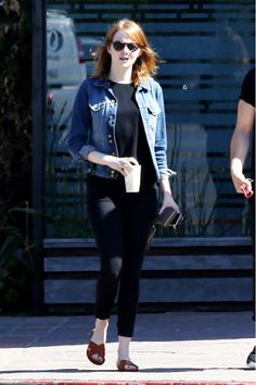 Emma Stone steps out in a black tee, black ankle jeans, brown sandals, denim jackets and sunglasses.