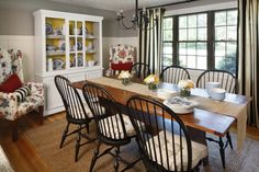 A Summer Coastal Cottage Dining Room featuring DIY striped outdoor fabric curtains + vibrant flowered DIY reupholstered wing back chairs. #bhgsummer