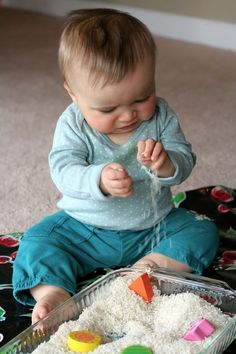Bij dit spel moet je eerst de rijst koken want als het kind de gewone rijst in zijn mondje steekt is het te hard en bij gekokte is het niet gevaarlijk.  Het kind kan voelen aan de rijst en er mee spelen en ook voelen aan de blokjes die je ook in de rijst kunt leggen.