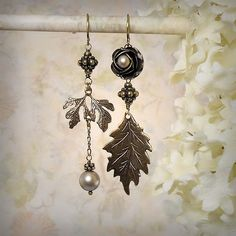 The Fallen series allows me to pull from a vast collection of leaf, flower and woodland-themed components. This rendition spotlights brass oak leaves, a lovely brass rose, Swarovski pearls in matte platinum, and granulated beads in antique brass ♥. Style: Asymmetric Earrings /