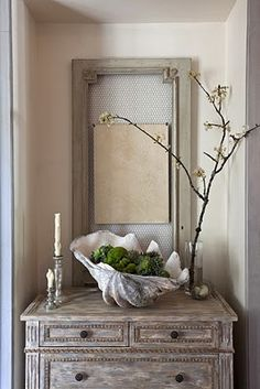 beautiful vignette with large clam shell & natural moss ball filler, branch, lt. grey mirror and chest... love