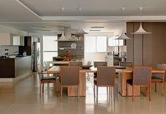A ideia era integrar cozinha e sala de jantar para dar liberdade ao morador, um jovem solteiro. Quando ele quiser esconder a cozinha, basta puxar as imensas portas de correr de laca marrom fosca. Projeto da arquiteta Flávia Gerab