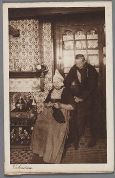 Man en een vrouw in dracht, zitten voor een betegelde schouw in een Volendams interieur. 1910-1920 #NoordHolland #Volendam