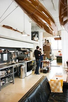 The kitchen was designed and installed by Amanda and Brian. The wooden kayaks hanging from the ceiling are handmade. (Melanie Biehle / Seattle Refined)