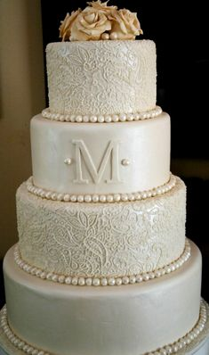 "Beautiful & Elegant Wedding Cake- need to talk to Anise about this one.  Could see if she could do gold flowers swirling down, and either the white lace with navy pearls or navy scroll with white pearls.  Like the round rather than the square. The monogram ""E"" Could be gold.  Could add in same scroll work as on invitations."