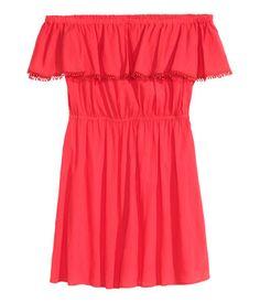 615c75da942d En kort klänning i krinklad bomullskvalitet. Klänningen har volang med  spetskant och resår upptill.