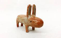 This is a four-legged kind of animal. It is a cheerful fella and a good listener. It is made of high fired clay, wearing a light gry-orange shiny glaze . Serious looking, but sweet and happy. 9cm / 3.5 inches Length - 7cm / 2.7 inches long Recycled shipping material when possible