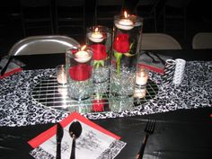 3 sizes of cyliders with a red roses submerged into the water and floating candle on top (roses poked into a dice size piece of florist oasis and covered with clear gems