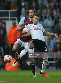 Morgan Schneiderlin of Manchester United in action with Andy Carroll of West Ham United during the Barclays Premier League match between West Ham United and Manchester United at the Boleyn Ground on May 10, 2016 in London, England.