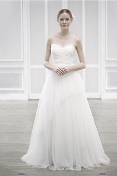 Sweetheart strapless Point d'Esprit over Organza gown with A-line skirt featuring soft gathers and a cascading asymmetrical panel.  Available in Soft White.
