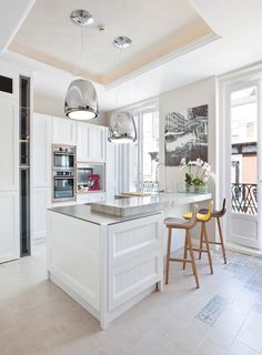 Mixed tile, wood trim around built-in oven etc, cream and white, coffered ceiling in a modern design. Steven Littlehales