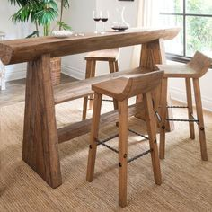 Solid seating. Made of reclaimed elm wood, the Hewn Wood Bar + Counter Stools take a classic stool design and update it with a lowered back and wrought iron detailing.